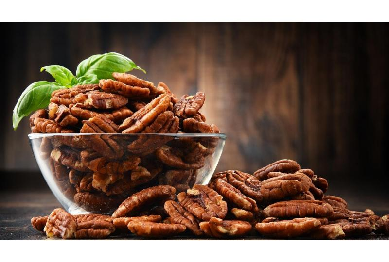 Fresh Pecans in Glass Bowl on Wooden Table Hero