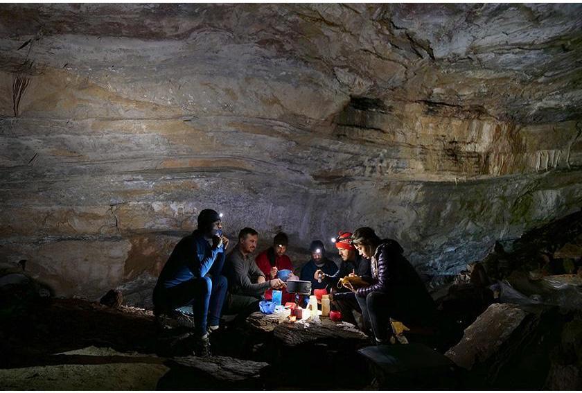 PESH Cavers gather around stone deep in cave