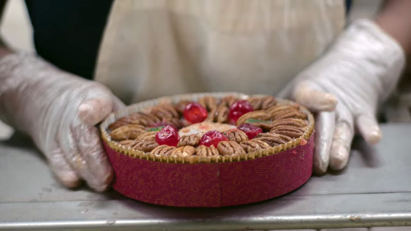Cake Decorator Displaying DeLuxe Fruitcake On Baking Line